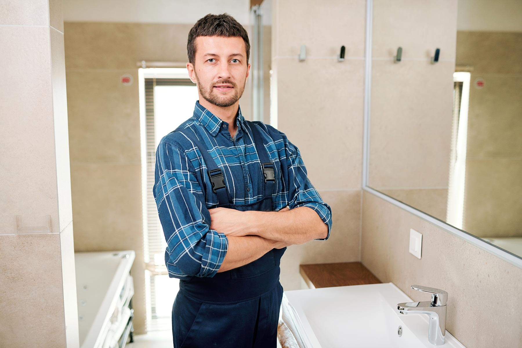 young-successful-plumber-in-workwear-standing-in-b-3P7U6YB.jpg